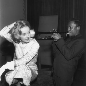 1957:  French actor Jeanne Moreau listens as American jazz musician Miles Davis (1926 - 1991) plays his trumpet, holding it to her ear. There is a mute attached to the bell of the trumpet.  (Photo by RDA/Getty Images)